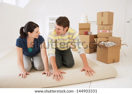 Happy young couple unrolling carpet in new home - stock photo