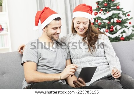 happy young couple use or watch something on tablet pc for christmas on sofa