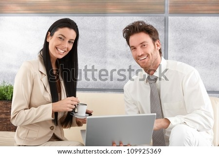 Happy young couple using laptop at home, smiling.