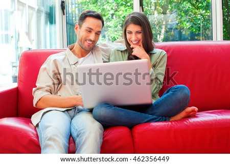 Happy young couple using laptop. Male and female partners are sitting on red sofa. They are in casuals at home.