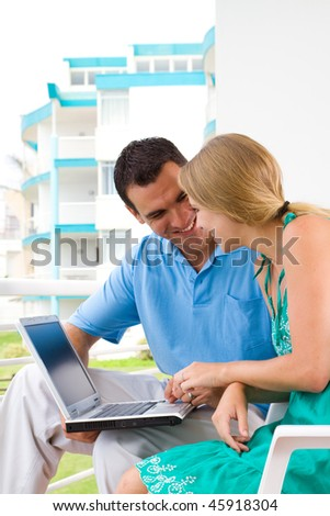 happy young couple using laptop on balcony