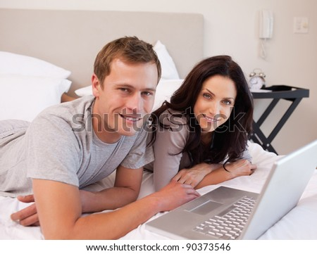 Happy young couple using laptop on the bed together