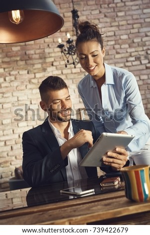 Happy young couple using tablet computer.