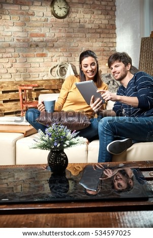 Happy young couple using tablet computer at home, smiling happy.