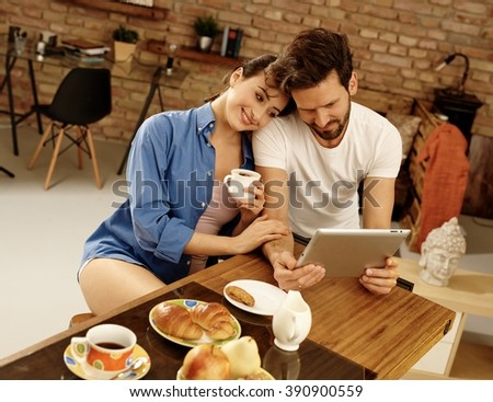 Happy young couple using tablet computer, having breakfast, enjoying time together. - stock photo