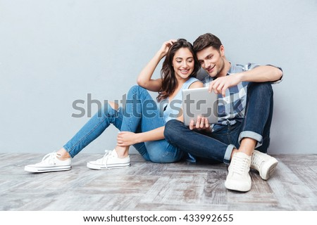 Happy young couple using tablet sitting on the floor at home isolated on gray background - stock photo