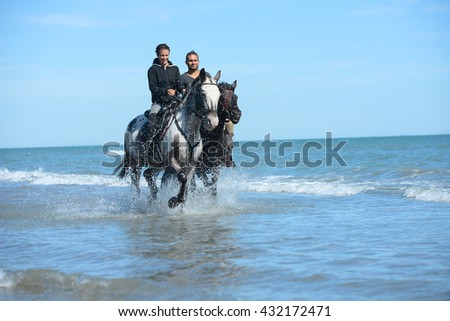 happy young couple vacation riding horses on the beach in a sunny summer day - stock photo