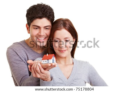 Happy young couple viewing a small house - stock photo
