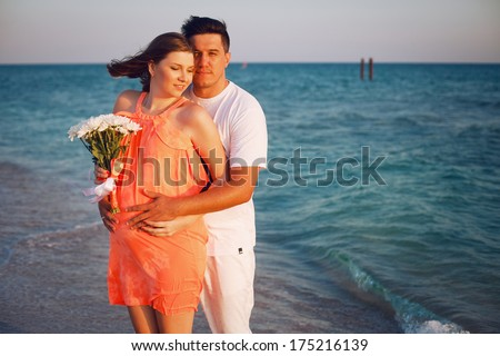 Happy young couple walking along the beach. Pregnant woman hugging her husband