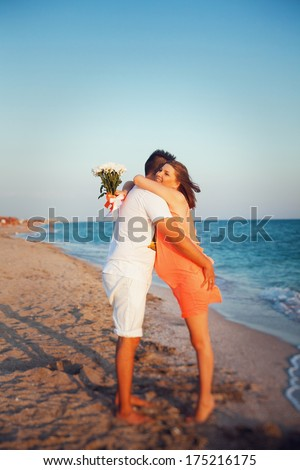 Happy young couple walking along the beach. Pregnant woman hugging her husband - stock photo