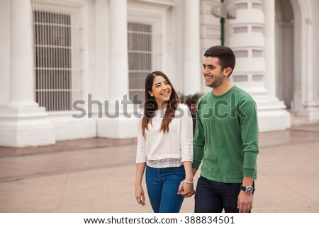 Happy young couple walking around the city together and holding hands - stock photo