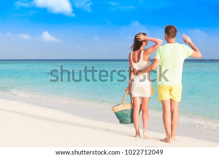 happy young couple walking by the beach