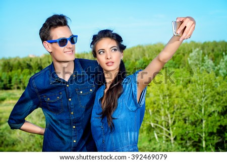Happy young couple walking in the park and making selfie by smart phone. Happy summer day.  - stock photo