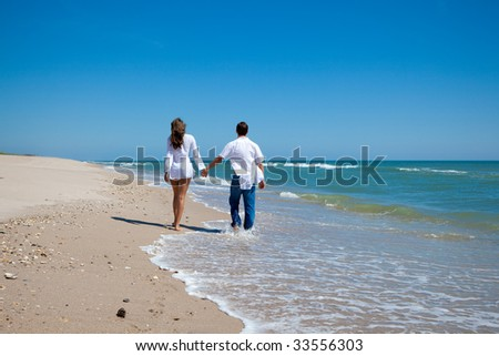 Happy young couple walking on a beach. - stock photo