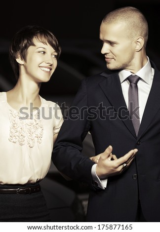Happy young couple walking on the night street - stock photo