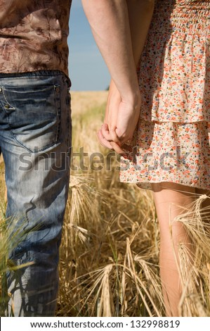 Happy young couple walking on wheat field - stock photo