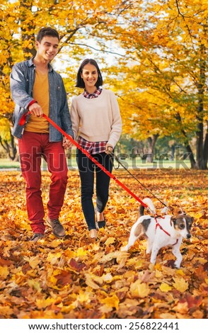 Happy young couple walking outdoors in autumn park with dogs - stock photo