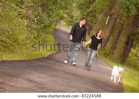 Happy young couple walking the dog - stock photo