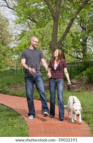Happy Young Couple Walking Their Dog - stock photo