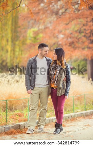 Happy young couple walking through the park in autumn - stock photo