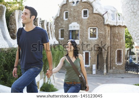 Happy young couple walking while holding hands at Barcelona