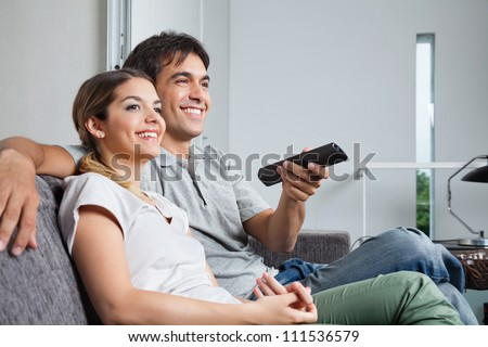 Happy young couple watching television together at home - stock photo
