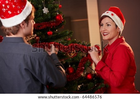 Happy young couple wearing santa claus hat, placing tinsel on christmas tree,  smiling.?