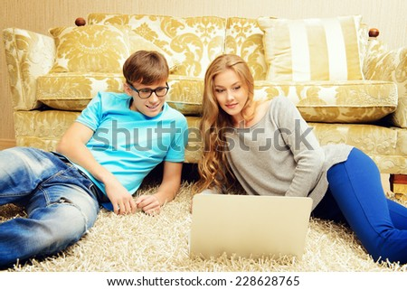 Happy young couple websurfing on internet with laptop. They sit in the cozy living room of their home.  - stock photo