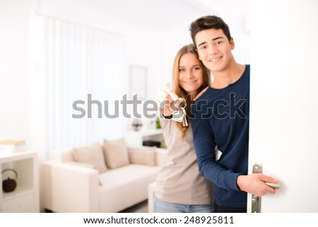 happy young couple welcome in  new house showing the door keys at entrance door - stock photo