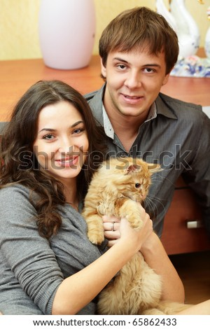 Happy young couple with a cat sitting at home - stock photo