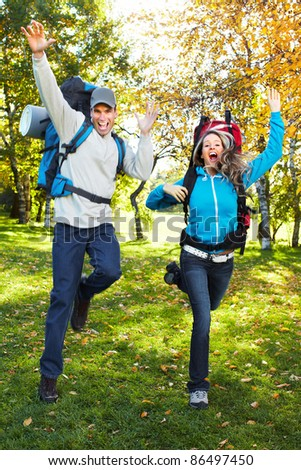 Happy young couple with backpacks in the park. Fall. - stock photo