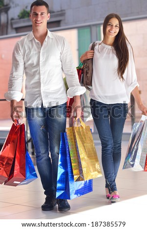 happy young couple with bags in shopping centre mall
