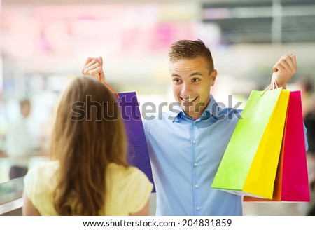 Happy young couple with bags in shopping mall - stock photo