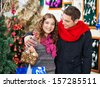 Happy young couple with bauble basket in Christmas store - stock photo