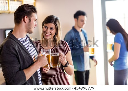 Happy young couple with beer mug in bar