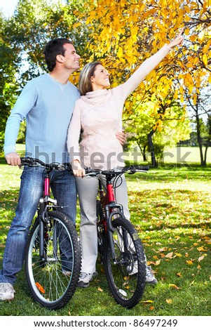 Happy young couple with bicycle in the park.