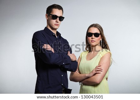 Happy young couple with black sunglasses. Studio shot.