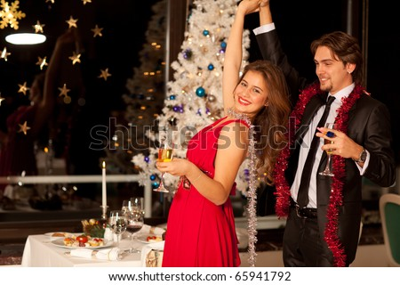 Happy young couple with champagne glasses in hand dancing at christmas, beautiful table and tree in the background, selective focus on girl. - stock photo