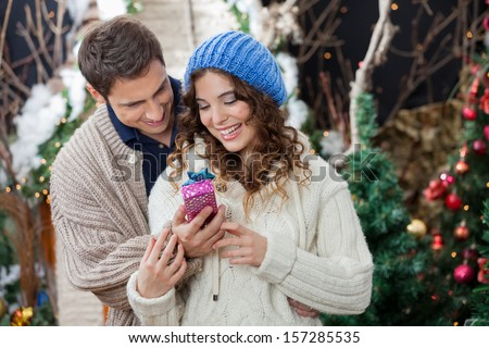 Happy young couple with Christmas present standing at store