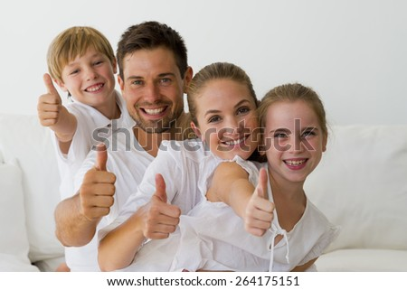 Happy young couple with daughter and son in a white atmosphere gesturing thumbs up. - stock photo