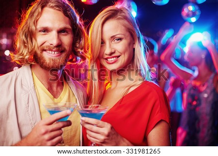 Happy young couple with flutes of champagne looking at camera