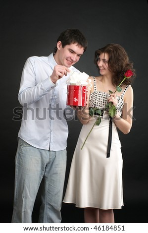 Happy young couple with gift and red rose isolated on a white background. - stock photo
