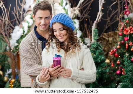 Happy young couple with gift box standing at Christmas store - stock photo
