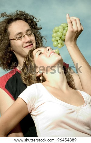 happy young couple with green grapes - stock photo