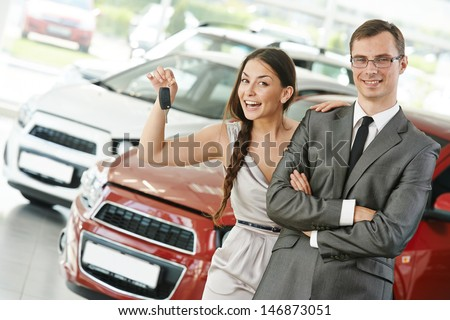Happy young couple with keys from new car after automobile purchase in dealer showroom - stock photo