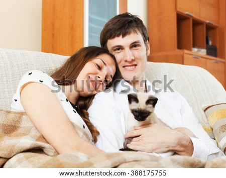 Happy young couple with kitten in home interior