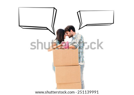 Happy young couple with moving boxes and piggy bank against speech bubble - stock photo