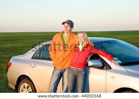 Happy young couple with new car - stock photo