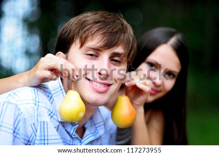 Happy young couple with pears in the form of earrings on picnic in park - stock photo