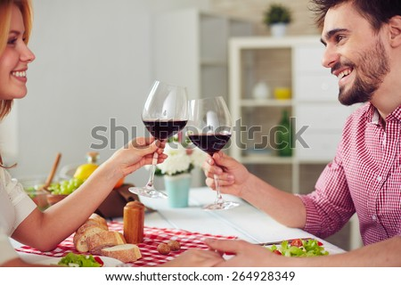 Happy young couple with red wine cheering by dinner - stock photo